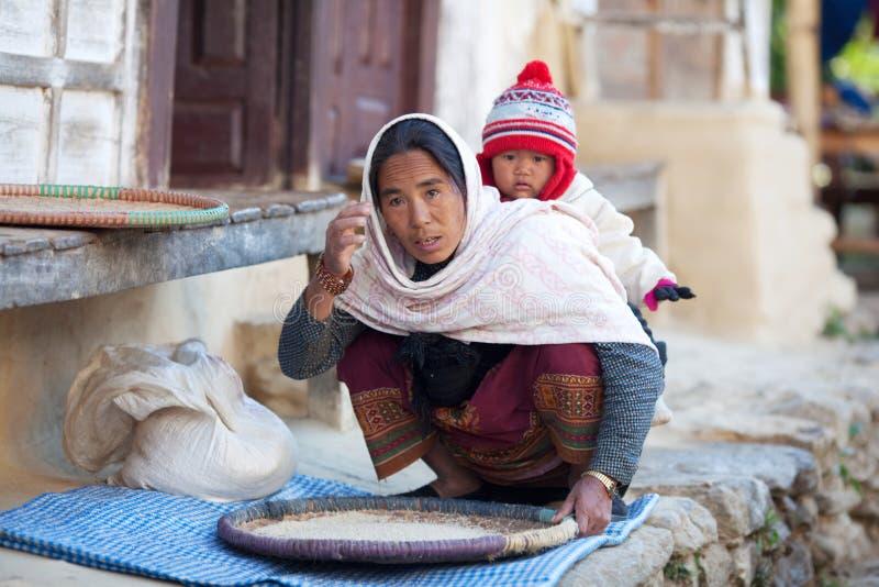 Mujer campesina en ropa nacional con el bebé fotos de archivo