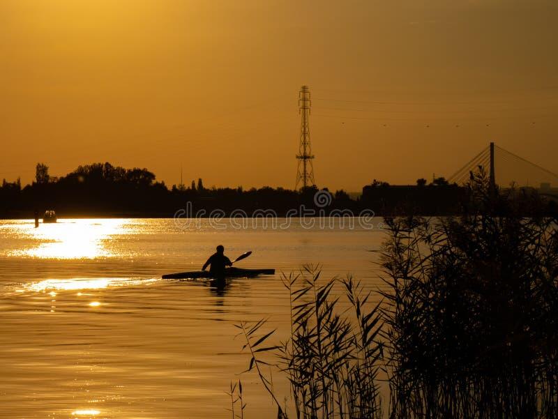 Mujer canoeing en la puesta del sol en el río Vistula, Polonia Paisaje y colores asombrosos fotos de archivo