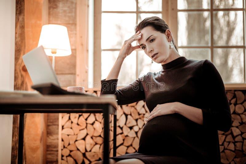 Mujer cansada agradable que se sienta delante de su ordenador portátil imagen de archivo