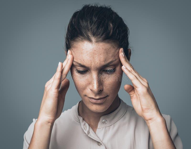 Mujer cansada con dolor de cabeza imagenes de archivo