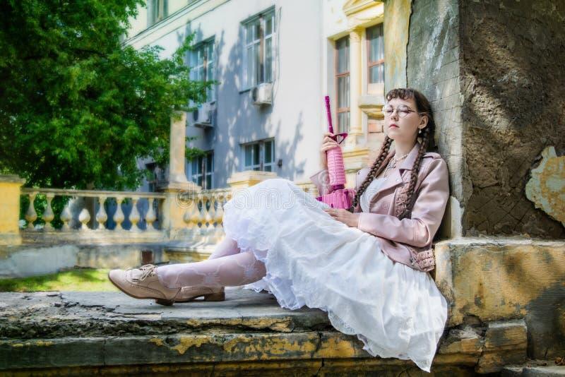 Mujer cansada con una reclinación rosada del rifle foto de archivo libre de regalías