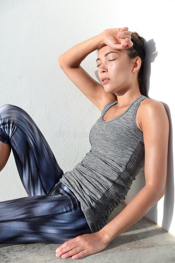 Mujer cansada de la aptitud que suda tomando una rotura del entrenamiento cardiio del difficul del entrenamiento fotos de archivo