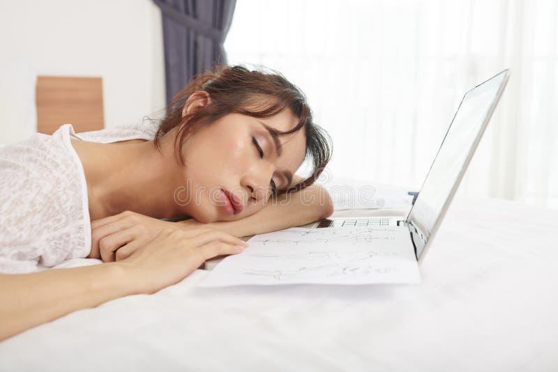 Mujer cansada de su trabajo sobre el ordenador port?til imágenes de archivo libres de regalías
