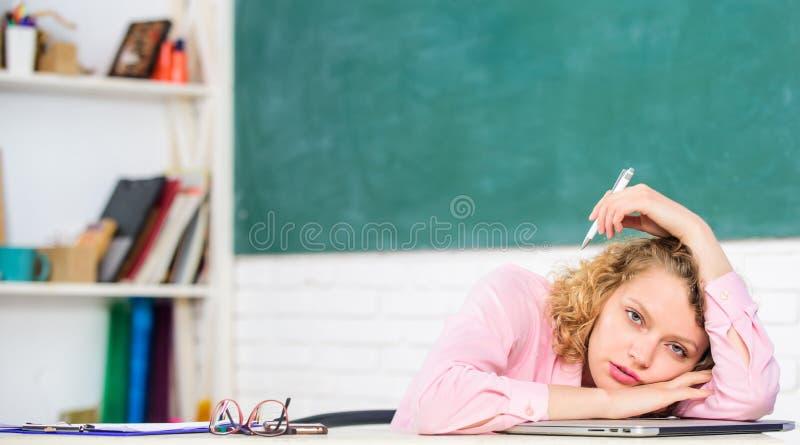 Mujer cansada en sala de clase de la escuela Profesor agotado después de día laborable duro Empleo agotador del pedagogo de la es foto de archivo libre de regalías