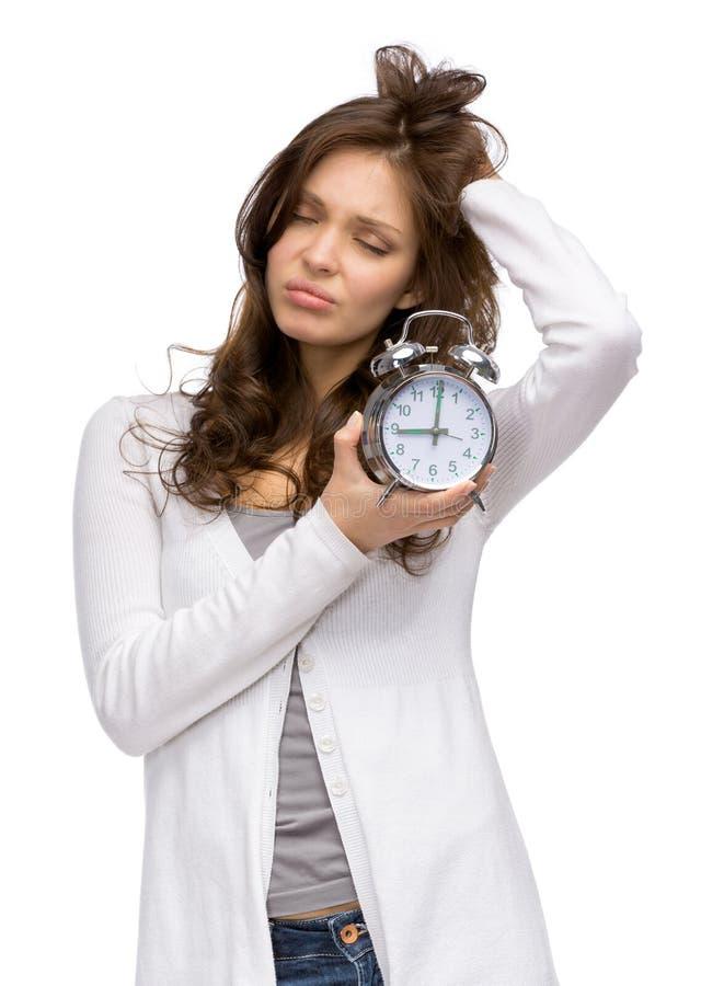 Mujer cansada que guarda el despertador fotos de archivo