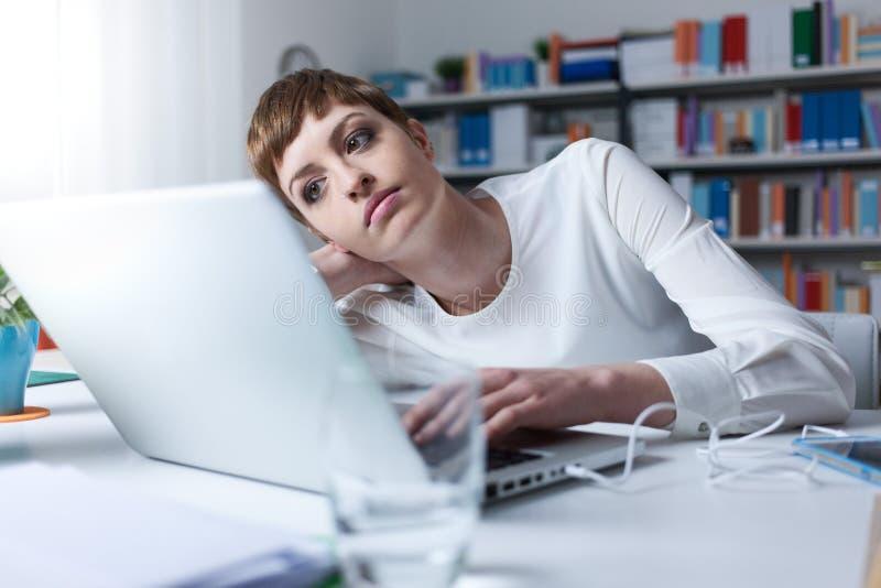 Mujer cansada que usa un ordenador portátil fotografía de archivo