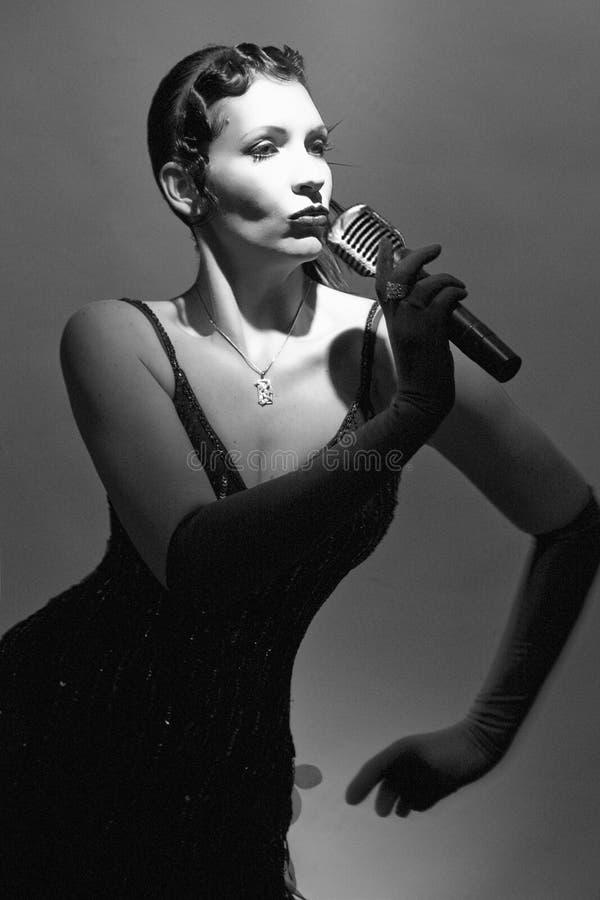 Mujer cantante con el micrófono imagen de archivo