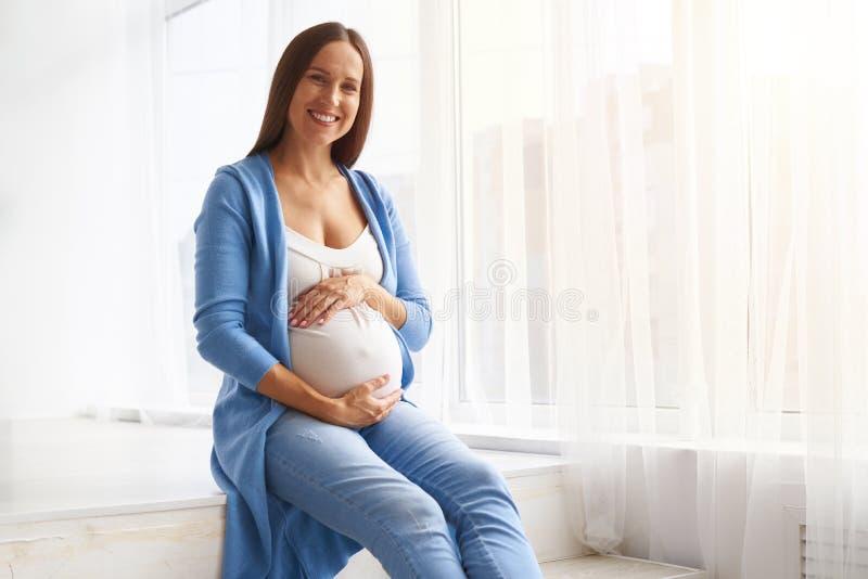 Mujer cariñosa que sostiene el vientre que se sienta contra ventana fotos de archivo