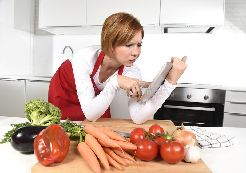 Mujer casera inexperta del cocinero en delantal en la cocina usando la tableta digital como referencia de la receta imagenes de archivo