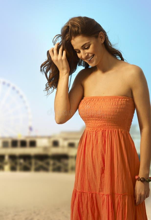 Mujer casual feliz en la playa que mira abajo fotos de archivo