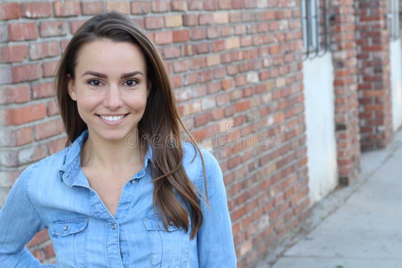 Mujer casual hermosa que sonríe - sobre un fondo de la pared de ladrillo con el espacio de la copia fotos de archivo