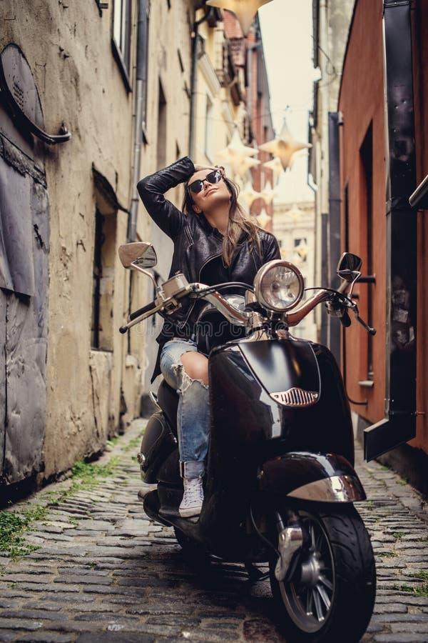Mujer casual impresionante que presenta con el scoote del moto fotos de archivo