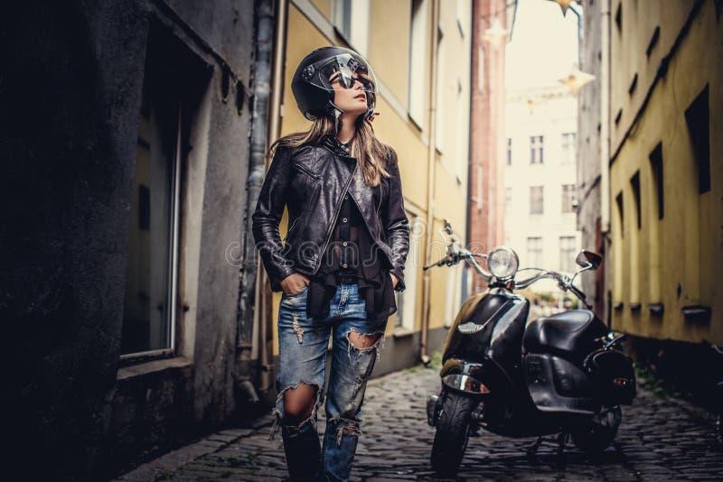 Mujer casual impresionante que presenta con el scoote del moto foto de archivo libre de regalías