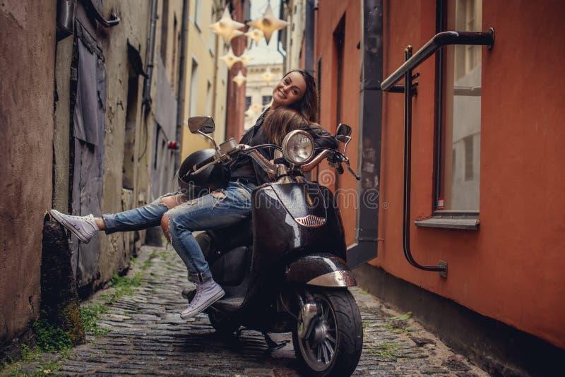 Mujer casual impresionante que presenta con el scoote del moto fotografía de archivo libre de regalías