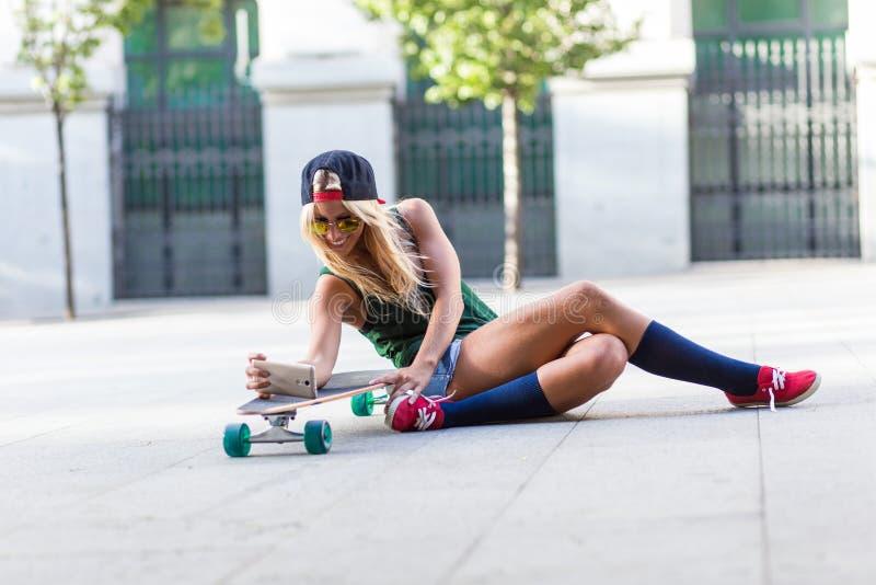 Mujer casual joven atractiva que toma un selfie en el piso fotografía de archivo libre de regalías