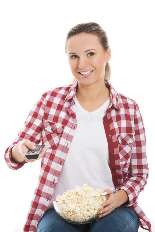 Mujer casual joven con teledirigido y cuenco de palomitas. foto de archivo