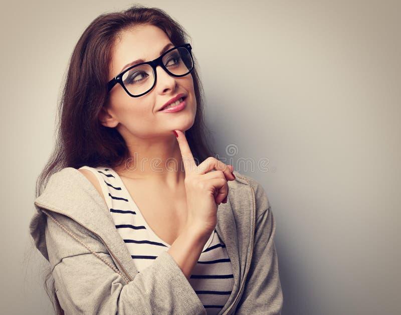 Mujer casual joven hermosa en vidrios que piensa con el und del finger foto de archivo libre de regalías