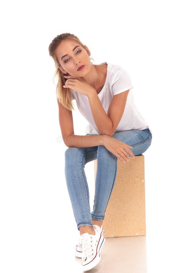Mujer casual joven pensativa que se sienta en la caja de madera imagen de archivo