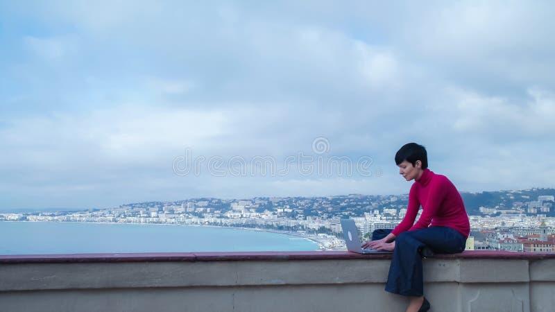 Mujer casual que mecanografía en el ordenador al aire libre fotografía de archivo