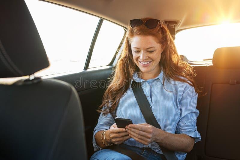 Mujer casual que usa smartphone en coche foto de archivo