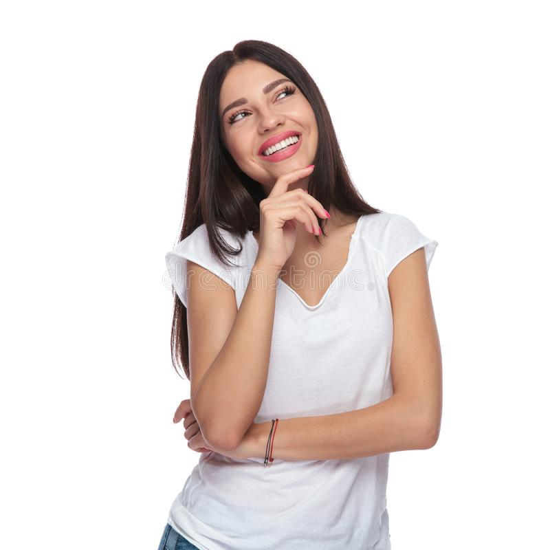 Mujer casual sonriente que mira para arriba para echar a un lado mientras que piensa imágenes de archivo libres de regalías