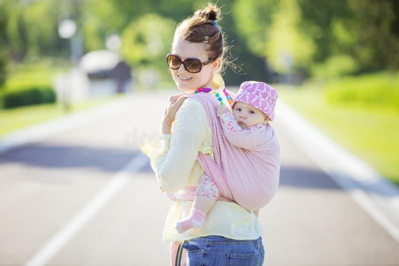 Mujer caucásica alegre que lleva a su hija del bebé en aire libre trasero fotografía de archivo libre de regalías