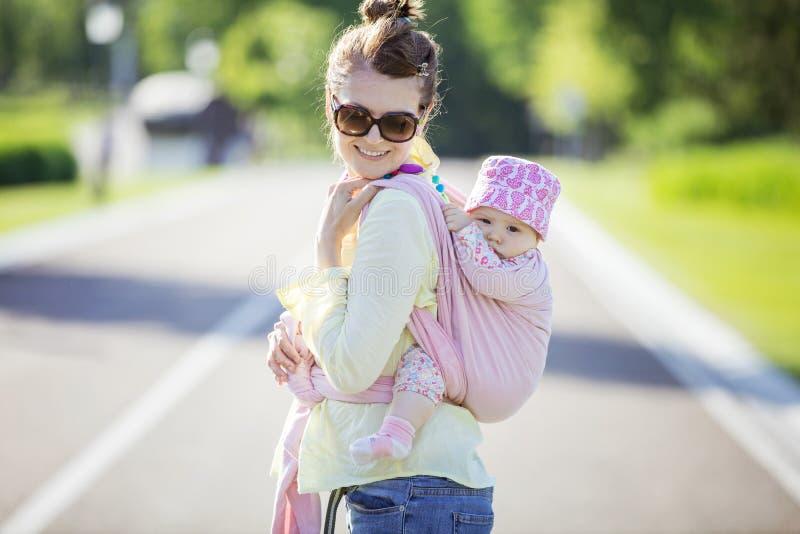 Mujer caucásica alegre que lleva a su hija del bebé en la parte posterior imagen de archivo