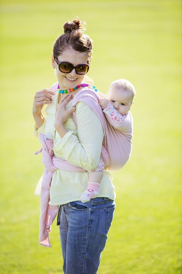 Mujer caucásica alegre que lleva a su hija del bebé en la parte posterior en parque de la primavera foto de archivo libre de regalías