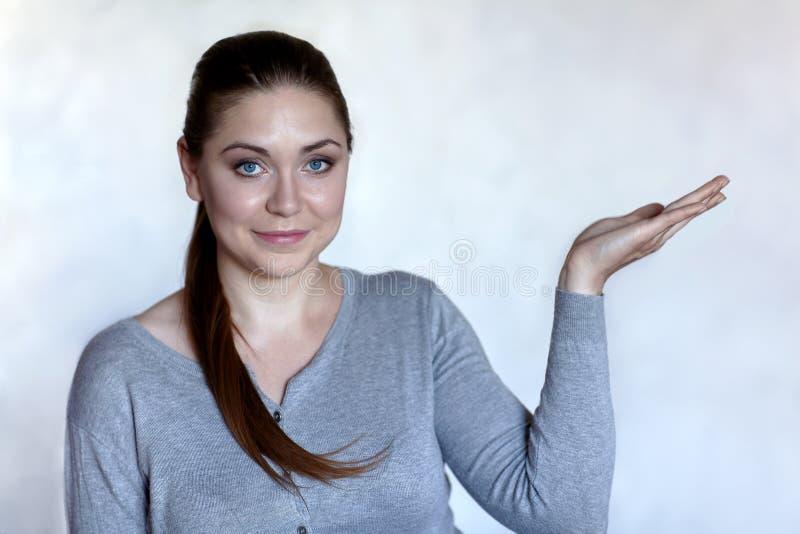 Mujer caucásica atractiva joven con los ojos azules y para arriba aumentados los brazos de las palmas en usted que ofrece algo La fotos de archivo