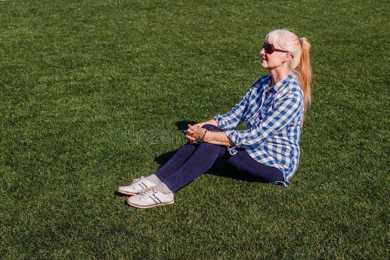 Mujer caucásica bien arreglada cincuenta años en una camisa y los vaqueros de tela escocesa que se sientan en la hierba imagen de archivo libre de regalías
