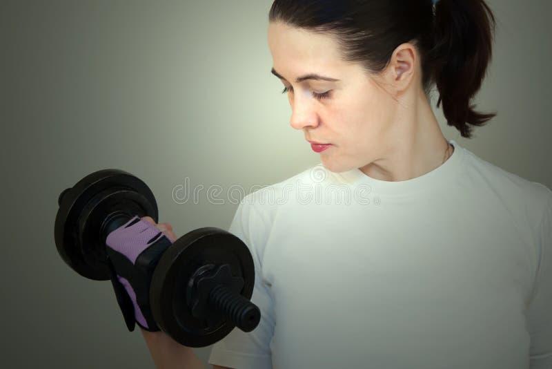 Mujer caucásica blanca atractiva del primer en la camiseta blanca que lleva a cabo pesas de gimnasia imágenes de archivo libres de regalías