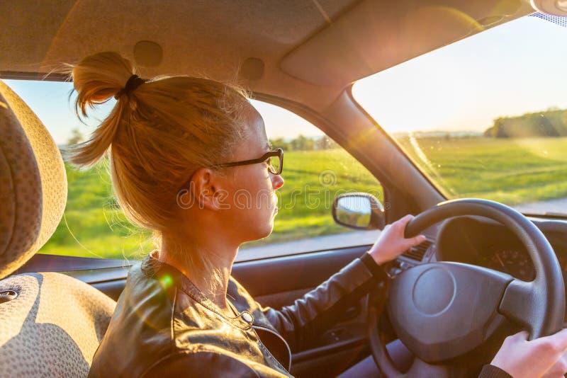 Mujer caucásica casual que conduce el vehículo de pasajeros para un viaje en campo imagen de archivo