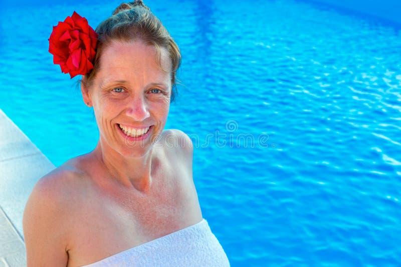 Mujer caucásica con color de rosa y toalla en la piscina imagenes de archivo