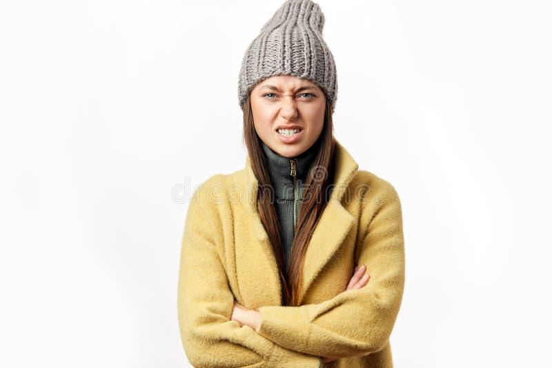 Mujer caucásica confusa y ofendida en la ropa colorida del invierno que presenta dentro foto de archivo