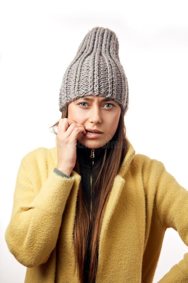 Mujer caucásica confusa y ofendida en la ropa colorida del invierno que presenta dentro imágenes de archivo libres de regalías