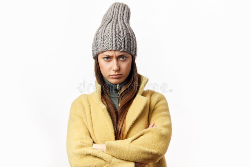 Mujer caucásica confusa y ofendida en la ropa colorida del invierno que presenta dentro fotos de archivo