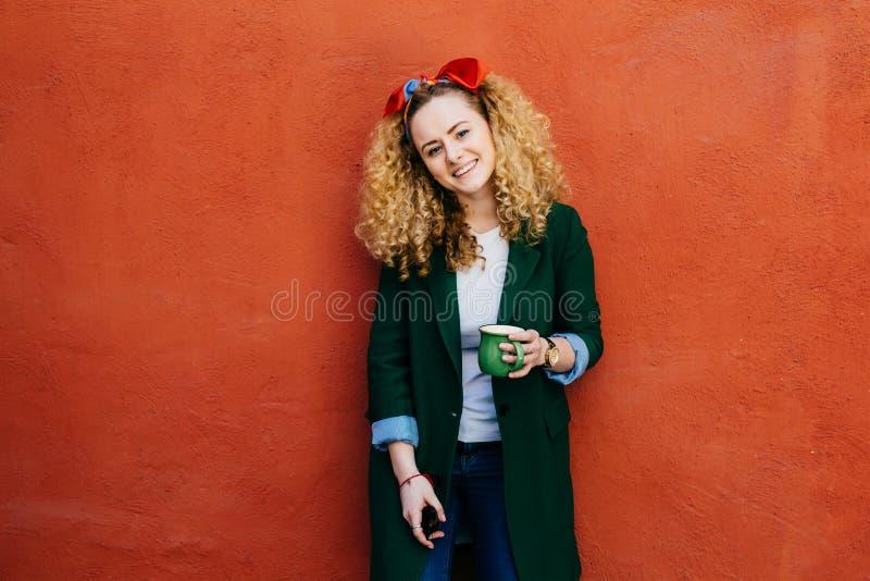 Mujer caucásica de moda joven con la venda que lleva del pelo rizado y la chaqueta elegante que sostienen la taza de café verde q fotos de archivo libres de regalías