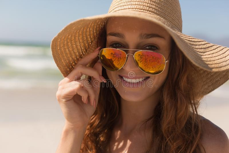 Mujer caucásica del bikini joven con el sombrero que mira sobre las gafas de sol foto de archivo libre de regalías