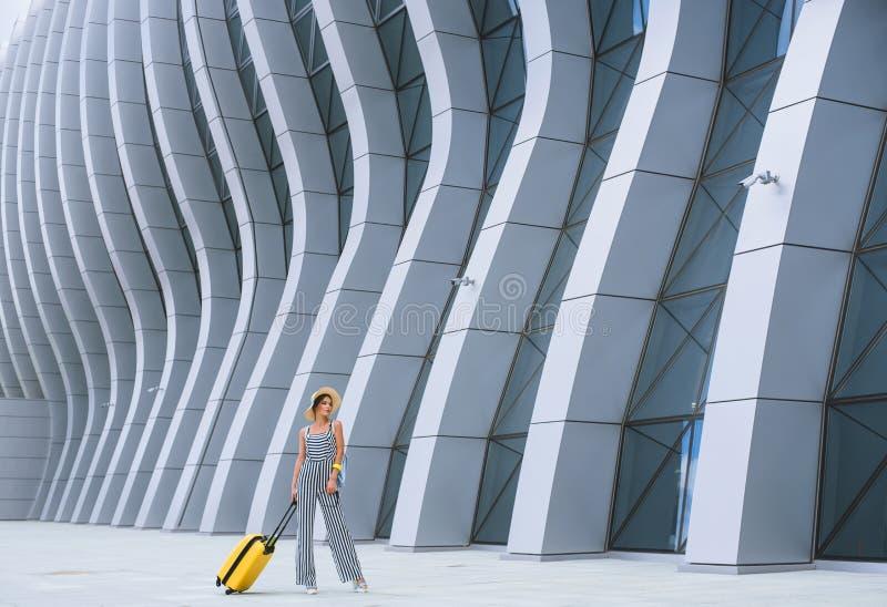 Mujer caucásica elegante joven en el aeropuerto con una maleta y un sombrero de paja imagenes de archivo