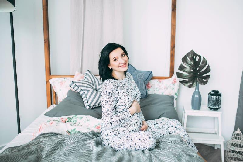 Mujer caucásica embarazada hermosa feliz con el vientre grande en los pijamas en el dormitorio, parrents futuros, esperando a un  fotos de archivo