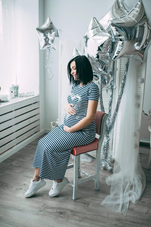 Mujer caucásica embarazada hermosa feliz con el vientre grande en vestido en la habitación del niño con los globos, parrents futu fotos de archivo