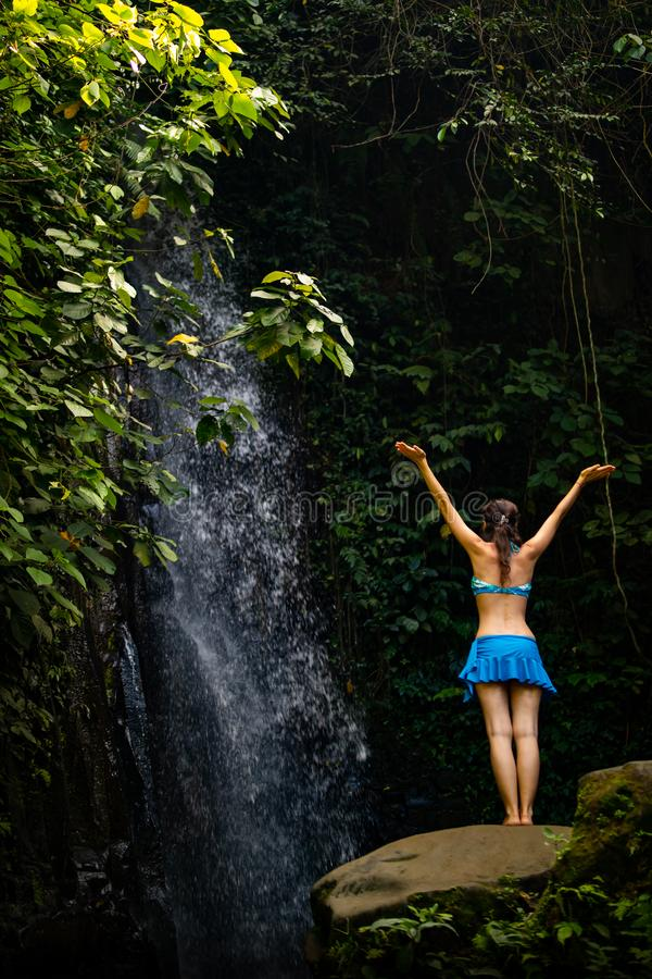 Mujer caucásica emocionada que aumenta los brazos delante de la cascada Visi?n desde la parte posterior Cerca de la cascada de Te imagen de archivo libre de regalías