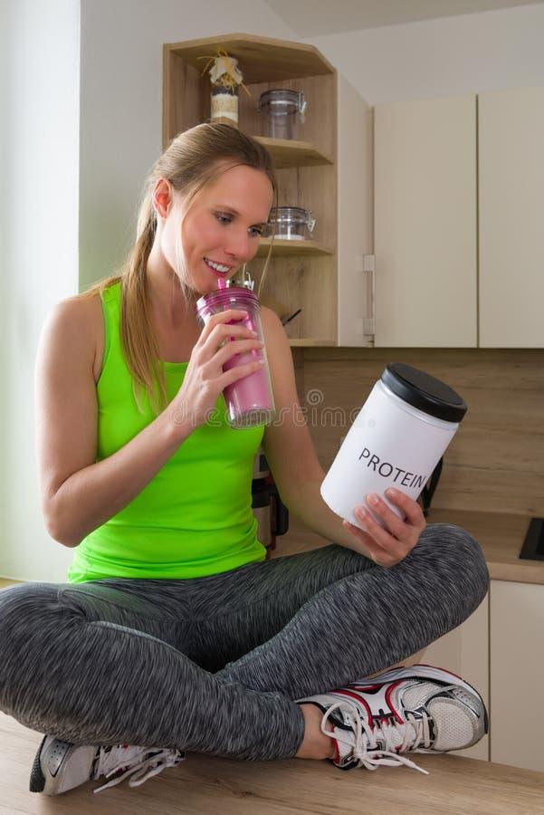 Mujer caucásica en sacudida de consumición de la proteína del traje de gimnasio en la cocina imagen de archivo