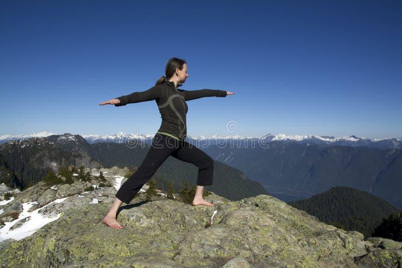 Mujer caucásica envejecida centro que lleva a cabo actitud del guerrero de la yoga de Hatha en picos de montaña de Snowcap del in imágenes de archivo libres de regalías