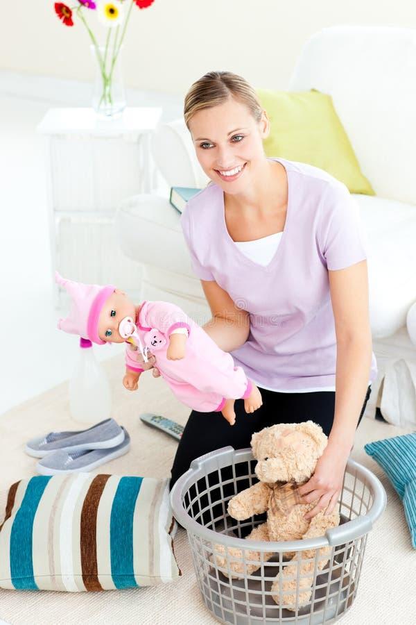 Mujer caucásica feliz que pone los juguetes en una cesta imagenes de archivo
