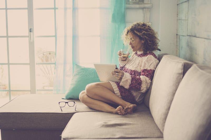Mujer caucásica hermosa de la Edad Media con el pelo rizado que trabaja en casa y que se relaja en el sofá con una tableta y Inte imagenes de archivo