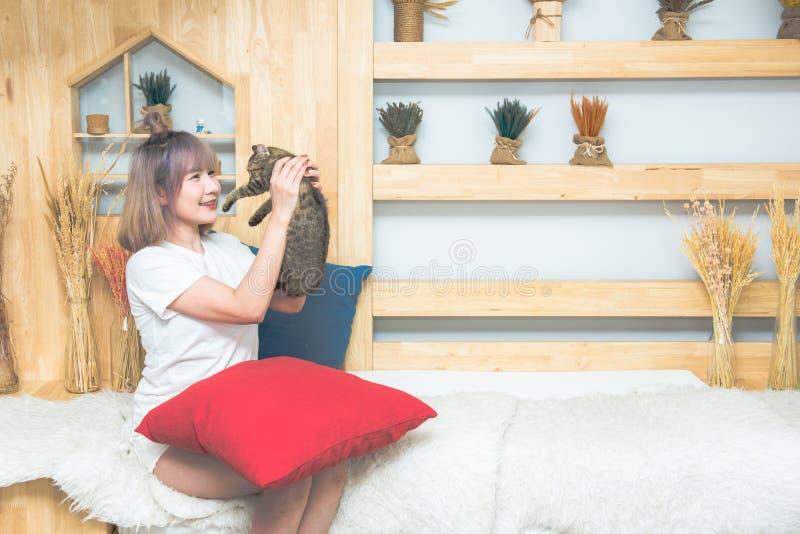 Mujer caucásica hermosa del asiático joven feliz que besa y que sostiene un gato El jugar con el animal dom?stico en casa Amor, i foto de archivo libre de regalías