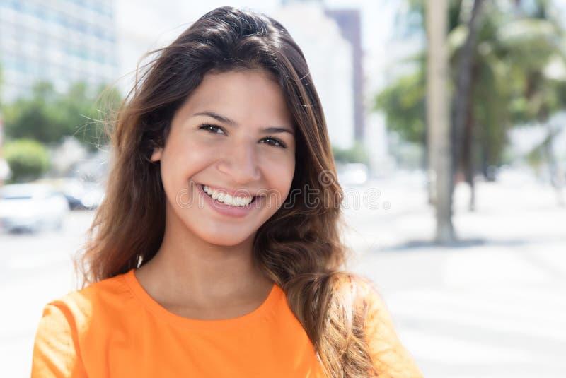 Mujer caucásica hermosa en una camisa anaranjada en la ciudad imagenes de archivo