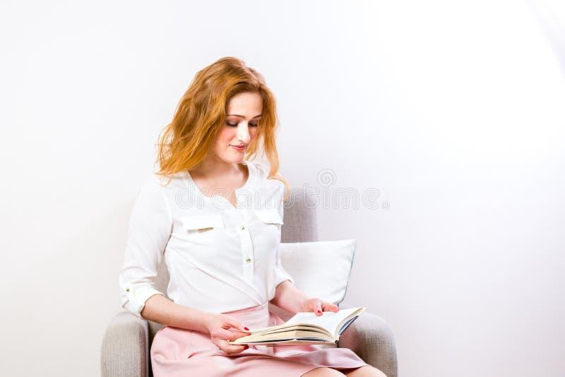 Mujer caucásica hermosa joven con el pelo y las pecas rojos magníficos largos en cara Muchacha del estudiante que se sienta en la fotos de archivo libres de regalías