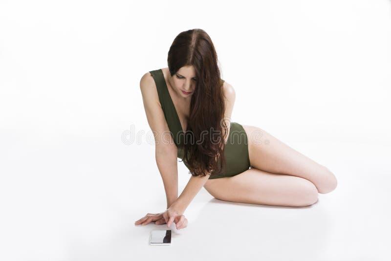Mujer caucásica hermosa joven con el teléfono móvil en estudio en el fondo blanco imágenes de archivo libres de regalías